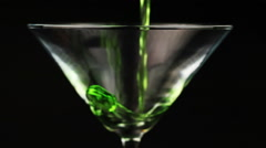 Pouring green cocktail in martini glass on black background Stock Footage