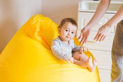 Smiling baby boy child sits on a chair - stock photo