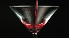 Pouring red cocktail in martini glass on black background - stock footage