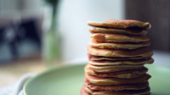 Pancakes stack on green plate at kitchen table. Close up of american pancakes - stock footage