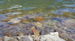 Slow Motion Waves Break on a Rocky Riverbank Stock Footage