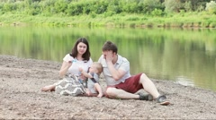 Mother, father and and son blowing air soap bubbles at the nature with river. Stock Footage
