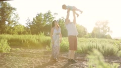 Happy young family with one year old child walking in the field at the sunset. Stock Footage
