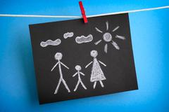 Drawing of a family on black piece of paper - stock photo