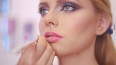 Make up artist applying lipstick with brush on pretty gorgeous woman lips Stock Footage