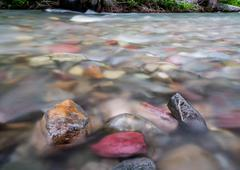 Water Rushes Past Exposed Rocks in Mountain Creek - stock photo