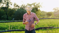 Young farmer in a hat and checked shirt talking on a cell phone at sunset. - stock footage