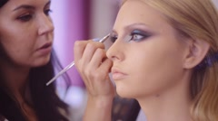 Makeup artist apply makeup to a models eyebrows. Perfect skin. Fashion and Stock Footage