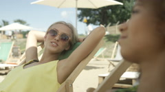Young beautiful girls sitting on sunbeds under umbrella and enjoying vacation. Stock Footage