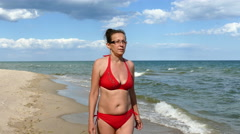 4K. Mature  Woman in  red bathing suit on  sea  beach Stock Footage