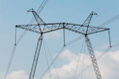 High-voltage transmission lines against the sky with clouds Stock Photos
