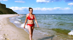 4K. Mature slender  Woman in  red bathing suit on  sea  beach Stock Footage