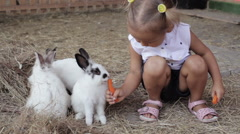 Cute little girl feeding rabbit from the hand Stock Footage