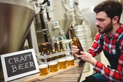 Young manufacturer examining beer in brewery Stock Photos