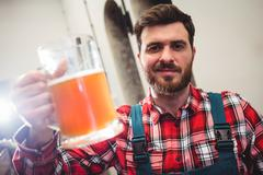 Portrait of manufacturer holding beer in jug at brewery Kuvituskuvat