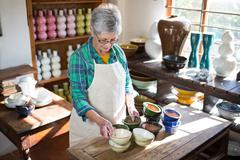 Female potter arranging bowl on worktop in pottery workshop Stock Photos