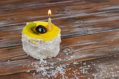 cupcake with candle on wooden background - stock photo