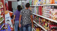 Latin Americans walk down goods isle in small store  (HD) Stock Footage