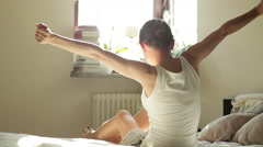 Beautiful brunette with arms outstretched sitting on bed HD Stock Footage