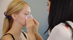Make-up artist cleaning skin on model's face. Concept of skin care Stock Footage