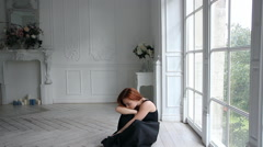 Young red-haired woman in a black dress sitting on the floor in the room. Stock Footage