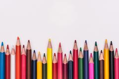 Colour pencils rainbow lay on white background - stock photo