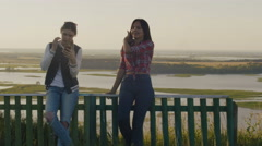 Two attractive girls friends young female standing on high hill and Stock Footage