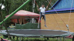 A boy jumping on the trampoline in the summer park Stock Footage