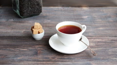 Cup of hot steaming black tea on wooden tabl Stock Footage