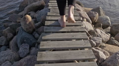 Young Woman Walking Out on Jetty in Slow Motion, Camera Following - Natural Stock Footage