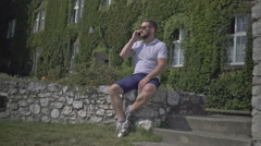 Young man talking by phone, sitting on the wall. - stock footage
