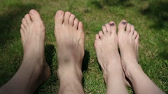 Male and female feet on grass Stock Footage