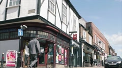 Shoppers walk passed Tudor building in St Peter Street, St Albans Stock Footage