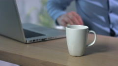 CU blank white coffee mug on the table, business man working in the bg Stock Footage