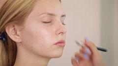Makeup artist applies eye shadow. Beautiful woman face. Perfect makeup. Close up Stock Footage