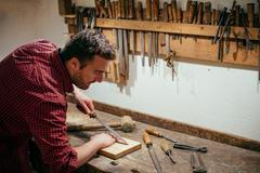 Carpenter working hard with tools in his carpentry - stock photo