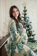 Pregnant woman happy at home near the Christmas tree during the celebration Stock Photos