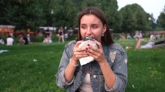Attractive girl eating with pleasure a fresh burger sitting on grass in park 4K Stock Footage