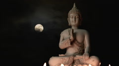 Seated Buddha statue lit by burning candles, composited moon timelapse bg Stock Footage