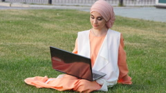 Beautiful muslim girl at park with notebook Stock Footage