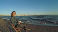 Girl on beach with coffee Stock Footage