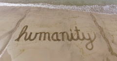 Aerial of the word humanity in the sand Stock Footage