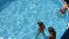 Swimming pool. Little girl jumping into the water in a pool. Slow motion. HD Stock Footage