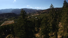 Aerial Crane Down Pine Trees Through The Valley/Rural Stock Footage
