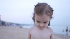 Child Playing on the Beach while Father Show how Sand Pours from Hands Stock Footage