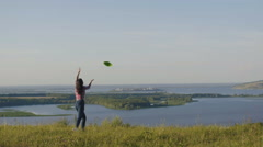 A Young Girls Throwing A green Frisbee at summer day on high hill Stock Footage