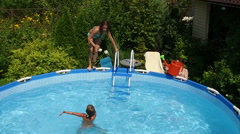 Swimming pool. Young girl jumping into the water in a pool. Slow motion. HD Stock Footage