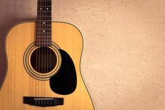 Acoustic guitar on beige background vintage wall Stock Photos