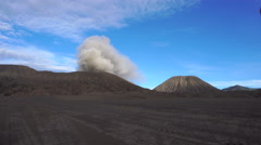Backpacker male traveler looking at active smoking Bromo volcano in Indonesia Stock Footage