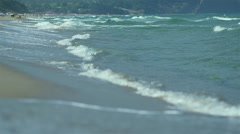 Waves crash on the shore of wild beach in slow motion Stock Footage